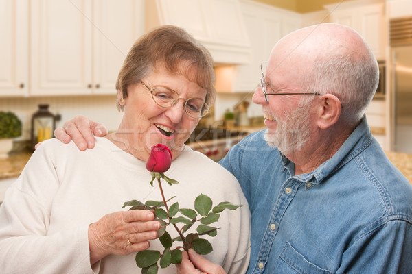 Stock photo: Happy Senior Adult Man Giving Red Rose to His Wife Inside Kitche