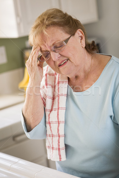 Senior Adult Woman At Kitchen Sink With Head Ache Stock photo © feverpitch