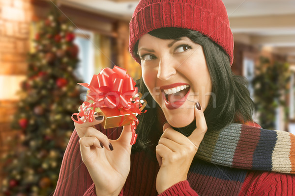 Stock photo: Woman Holding Wrapped Gift in Christmas Setting