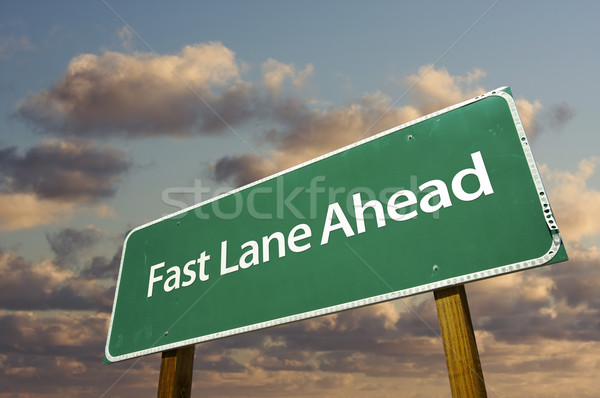 Stock photo: Fast Lane Ahead Green Road Sign Over Clouds
