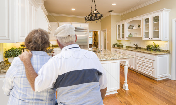 Stock photo: Senior Couple Looking Over Beautiful Custom Kitchen