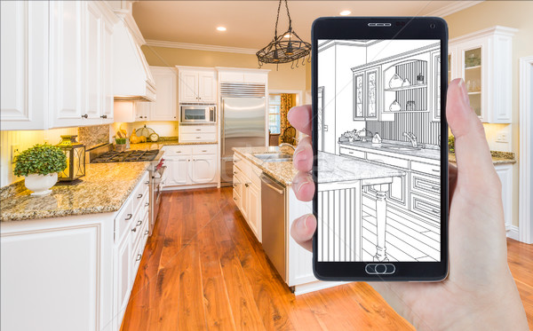 Hand Holding Smart Phone Displaying Drawing of Kitchen Photo Beh Stock photo © feverpitch