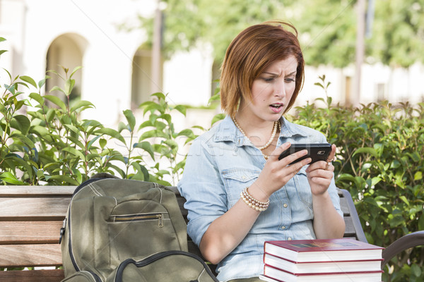 Stunned Young Female Student Outside Texting on Cell Phone Stock photo © feverpitch