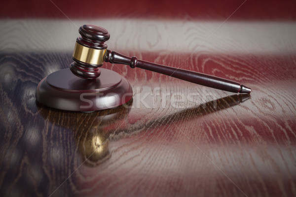 Wooden Gavel Resting on Flag Reflecting Table Stock photo © feverpitch