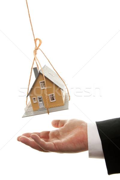 Businessman's Hand Under Dangling House Stock photo © feverpitch