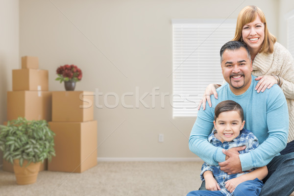 Mixed Race Family with Son in Room with Packed Moving Boxes Stock photo © feverpitch