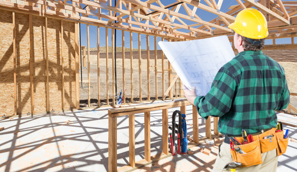 Contractor with hard Hat and Plans Standing Inside Construction  Stock photo © feverpitch