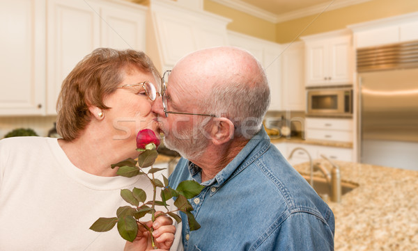Happy Senior Adult Man Giving Red Rose to His Wife Inside Kitche Stock photo © feverpitch