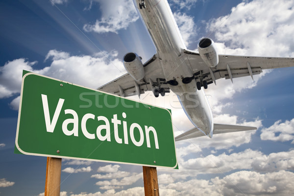Vacation Green Road Sign and Airplane Above Stock photo © feverpitch
