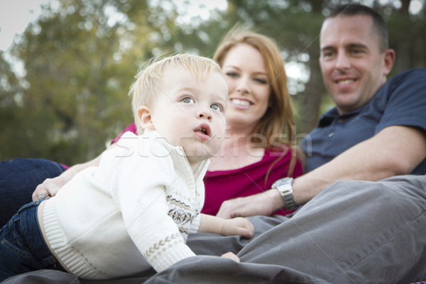 Cute Child Looks Up to Sky as Young Parents Smile Stock photo © feverpitch