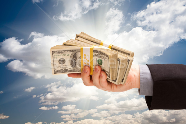 Male Hand Holding Stack of Cash Over Clouds and Sky Stock photo © feverpitch
