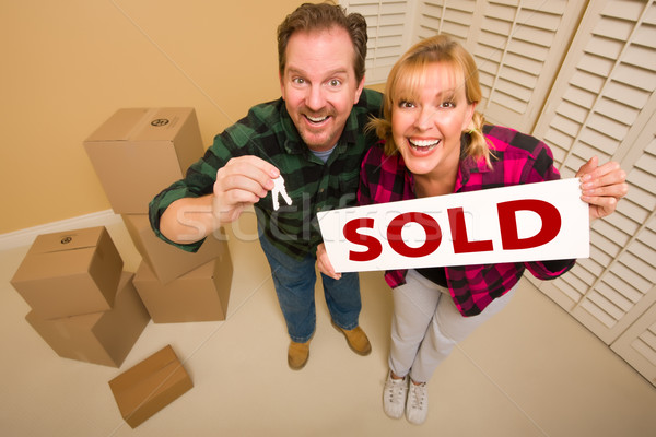 Goofy Couple Holding Key and Sold Sign Surrounded by Boxes Stock photo © feverpitch