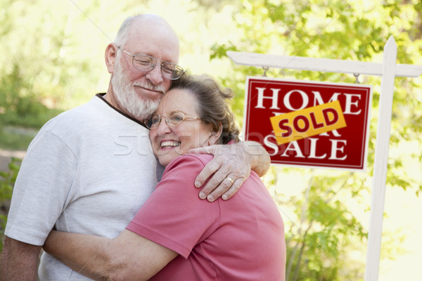 Senior Couple in Front of Sold Real Estate Sign Stock photo © feverpitch