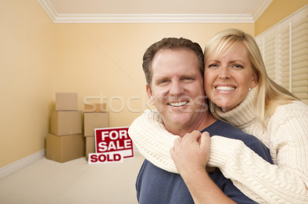 Couple in New House with Boxes and Sold Sale Sign Stock photo © feverpitch