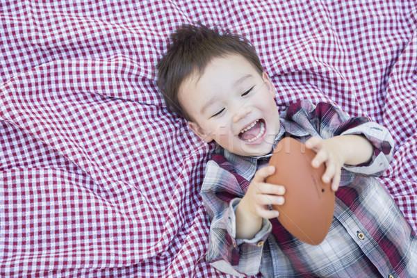 Jonge halfbloed jongen spelen voetbal picknickdeken Stockfoto © feverpitch