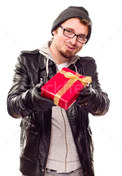 Warmly Dressed Young Man Handing Wrapped Gift Out Stock photo © feverpitch