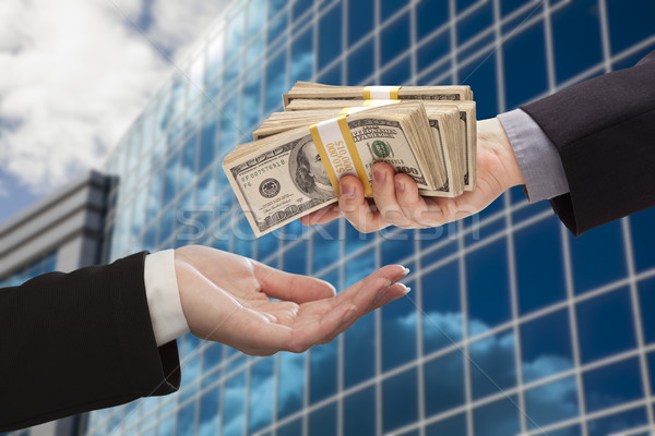 Male Handing Stack of Cash to Woman with Corporate Building Stock photo © feverpitch