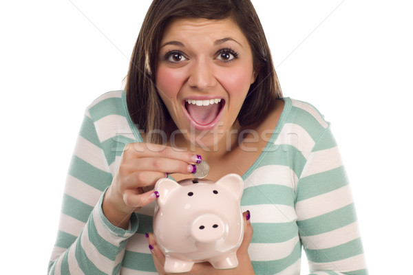 Ethnic Female Putting Coin Into Piggy Bank on White Stock photo © feverpitch