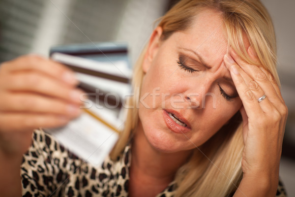 Stock photo: Upset Woman Holding Her Many Credit Cards