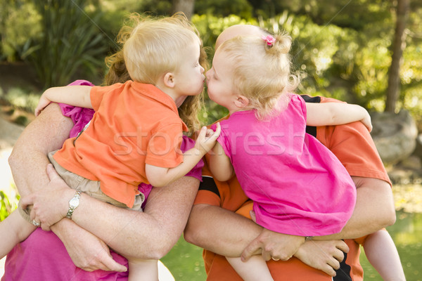Mom and Dad Holding Kissing Brother and Sister Toddlers Stock photo © feverpitch