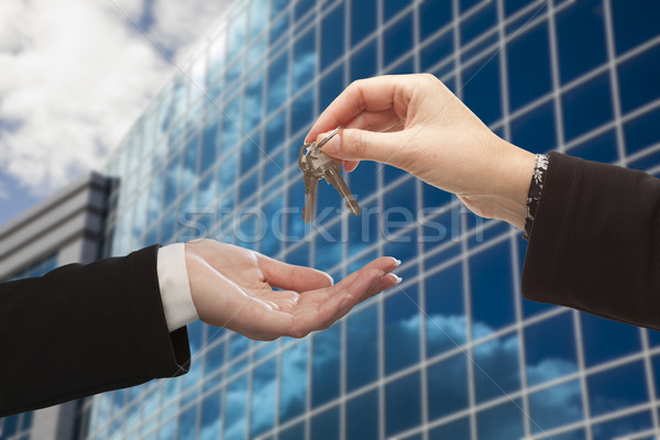 Female Handing Over the Keys in Front of Corporate Building Stock photo © feverpitch
