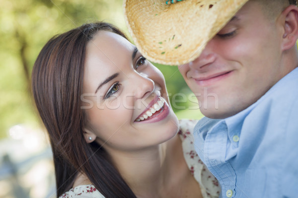 Mixed Race Romantic Couple with Cowboy Hat Flirting in Park Stock photo © feverpitch