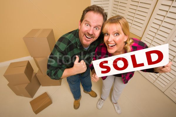 Goofy Couple Holding Sold Sign Surrounded by Boxes Stock photo © feverpitch