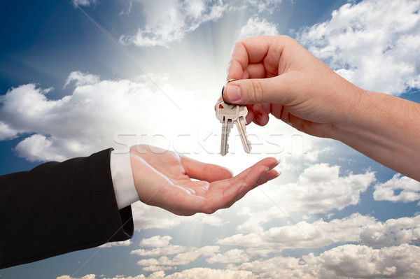 Male Handing Keys to Female Over Clouds and Rays Stock photo © feverpitch