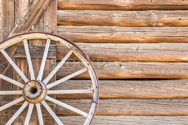 Abstract of Vintage Antique Log Cabin Wall and Wagon Wheel. Stock photo © feverpitch