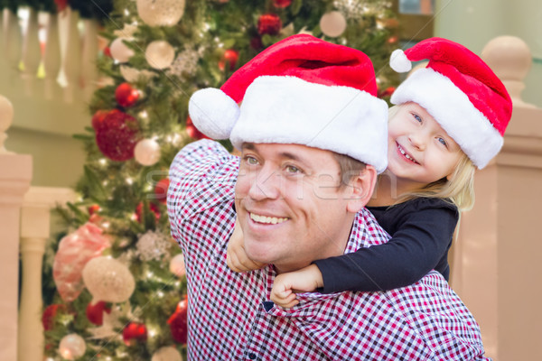 Father and Daughter Wearing Santa Hats In Front of Decorated Chr Stock photo © feverpitch