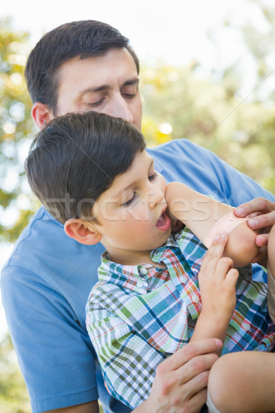 Loving Father Puts a Bandage on the Elbow of His Young Son in th Stock photo © feverpitch