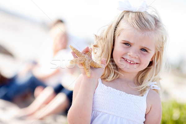 Adorable peu fille starfish plage Photo stock © feverpitch