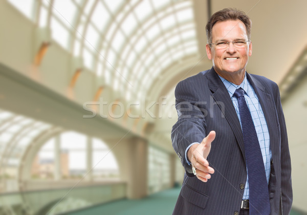 Businessman Reaching for Hand Shake Inside Corporate Building Stock photo © feverpitch