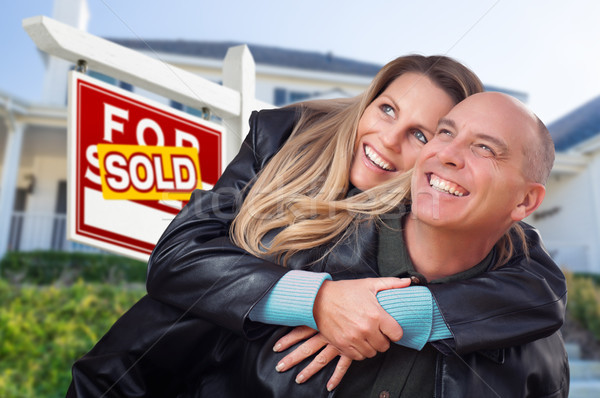 Happy Couple Hugging in Front of Sold Real Estate Sign and House Stock photo © feverpitch