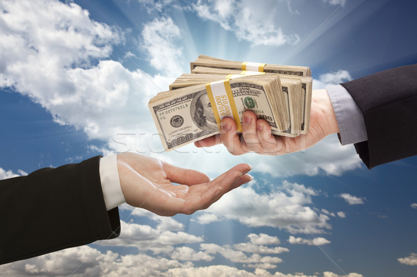 Handing Over Cash with Dramatic Clouds and Sky Stock photo © feverpitch
