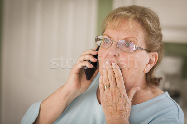 Shocked Senior Adult Woman on Cell Phone in Kitchen Stock photo © feverpitch