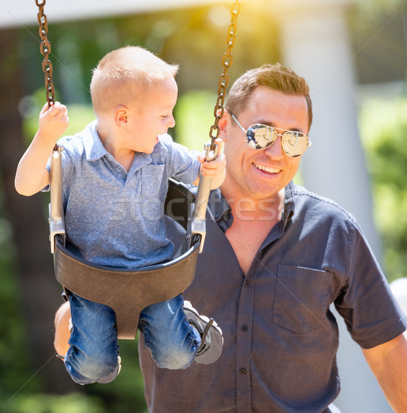 Happy Young Boy Having Fun On The Swings With His Father At The  Stock photo © feverpitch