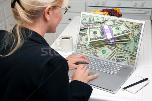 Woman In Kitchen Using Laptop - Money Stock photo © feverpitch