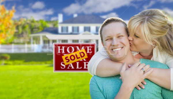 Happy Couple In Front Sold Real Estate Sign and House Stock photo © feverpitch