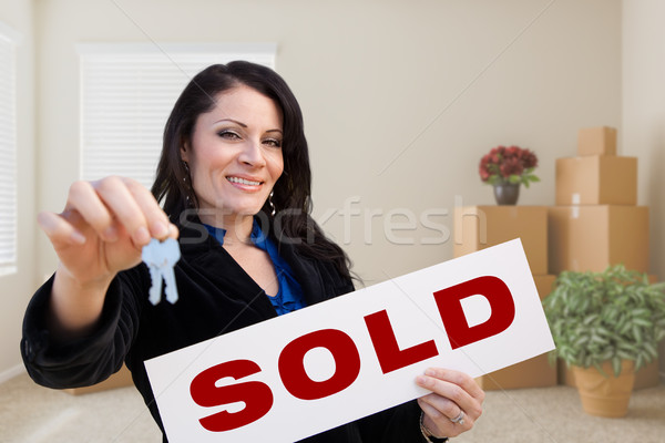 Hispanic Female Real Estate Agent with Sold Sign and Keys in Roo Stock photo © feverpitch