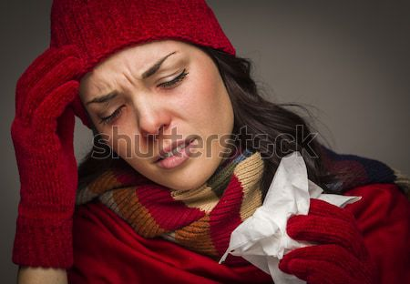 Sick Mixed Race Woman Blowing Her Sore Nose With Tissue Stock photo © feverpitch
