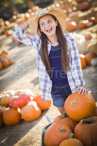 Preteen Girl Playing with a Wheelbarrow at the Pumpkin Patch Stock photo © feverpitch