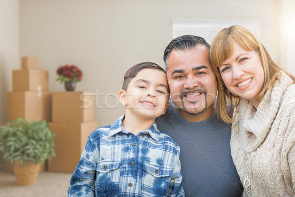 Mixed Race Family In Empty Room With Moving Boxes and Plants. Stock photo © feverpitch