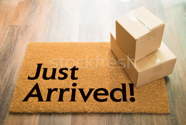 Just Arrived Welcome Mat On Wood Floor With Shipment of Boxes Stock photo © feverpitch