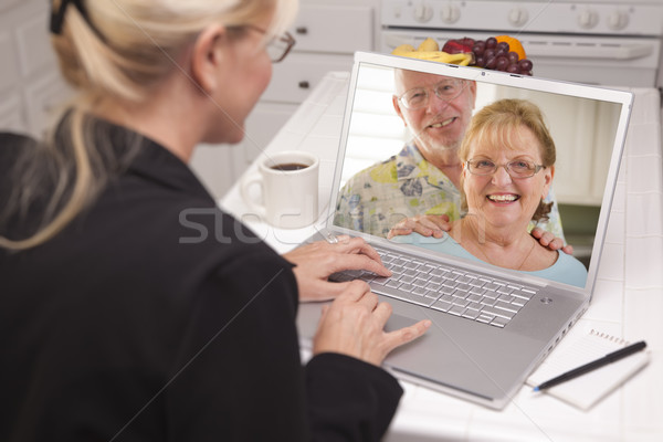 Stock photo: Woman In Kitchen Using Laptop - Online with Senior Couple