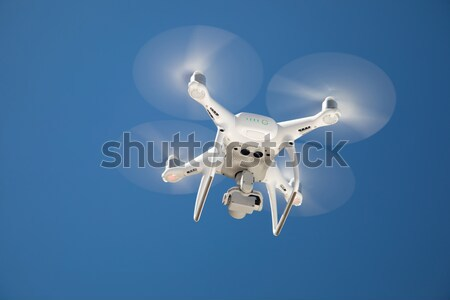 Unmanned Aircraft System (UAV) Quadcopter Drone In The Air. Stock photo © feverpitch