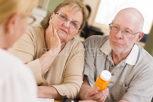 Stock photo: Doctor or Nurse Explaining Prescription Medicine to Senior Coupl