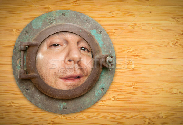 Stock photo: Antique Porthole on Bamboo Wall with Funky Man Looking Through