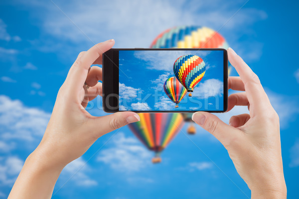 Female Hands Holding Smart Phone Displaying Photo of Blue Sky wi Stock photo © feverpitch
