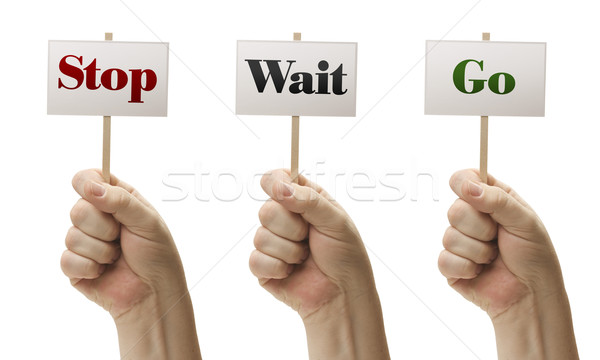 Three Signs In Fists Saying Stop, Wait and Go Stock photo © feverpitch